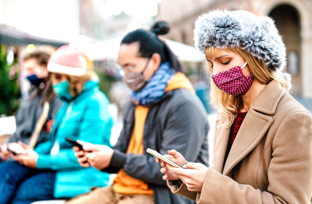 Blond girl using smart phone covered by mask on Covid third wave