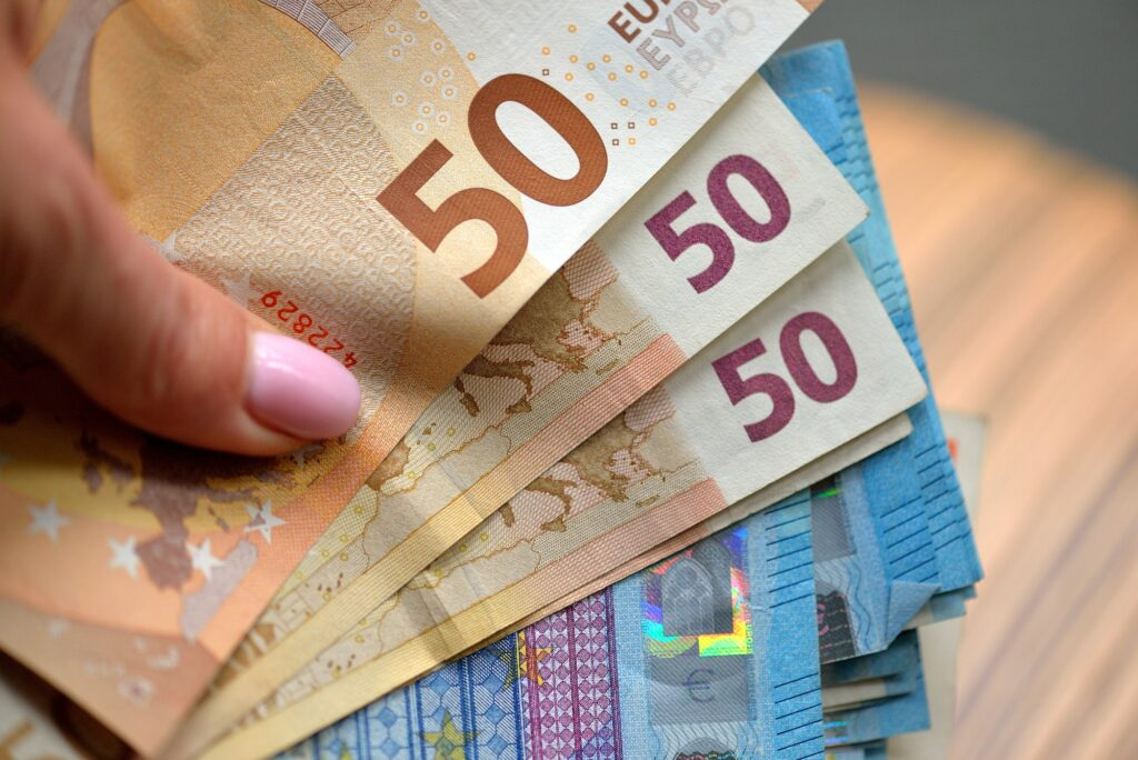 Hand holding 50 and 20 Euro banknotes money (EUR), currency of European Union.